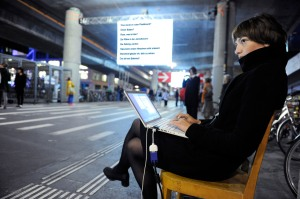 Photo of young woman typing on a laptop in a busy subway station.