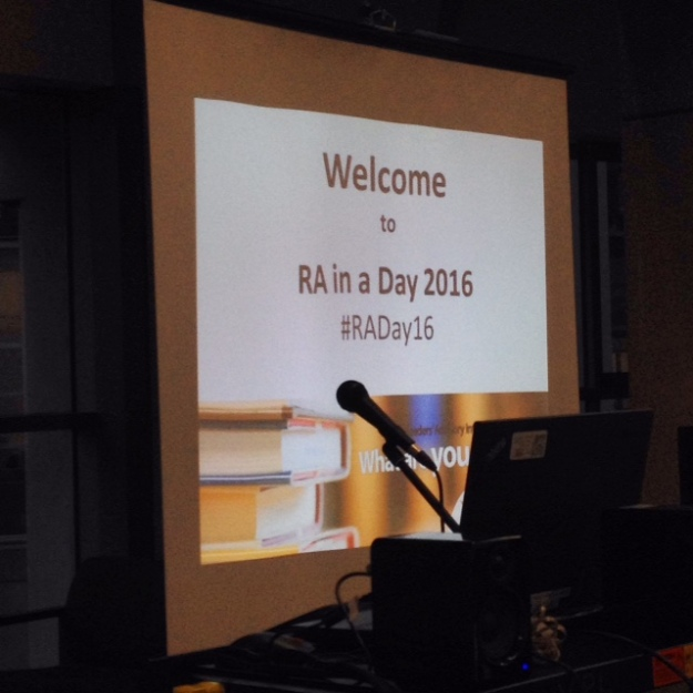 "A sign stating ""Welcome to RA in a Day 2916"" behind a silhouette of a microphone"